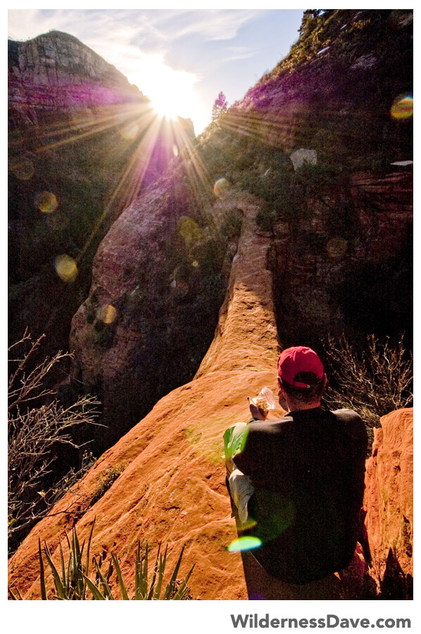Trail Sherpa sitting above Vultee Arch at Sunset in Sedona